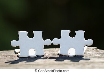 2 white pieces of puzzle stand on wooden table isolated on black background, concept of connecting