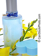 a bottle of fresh scent with flowers and heart-shaped soap on a white background