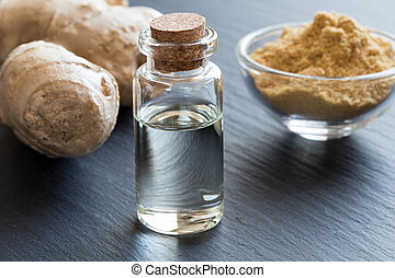 A bottle of ginger essential oil with fresh and dried ginger