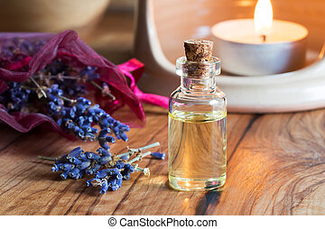 A bottle of lavender essential oil with dried lavender twigs