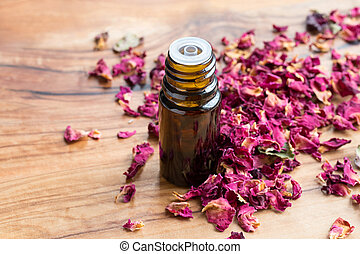 A bottle of rose essential oil with dried rose petals