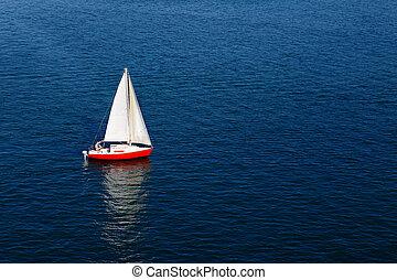 A lone white sail of a red sailboat on a calm blue sea