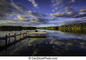 A beautiful southern sunset reflecting on a calm lake in the southern United States of America during the fall. Showing leaves changing colors. with a wooded pier, mooring balls and a floating trampoline.
