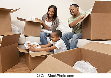 African American family, parents and son, unpacking boxes and moving into a new home, The adults are unpacking crockery and houseware, the child is unpacking a toy airplane.