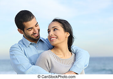 Arab casual couple cuddling happy with love on the beach with the horizon and the sea in the background