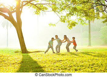 Happy Asian family playing together at outdoor park