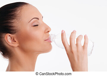 Close up of beautiful woman drinking water from bottle. She closed her eyes with enjoyment. Isolated on background