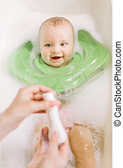 Baby swimming with green neck swim ring. mom squeezes shampoo out of the tube