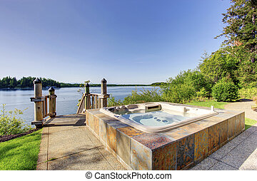 Backyard area with hot tub and awesome water view.
