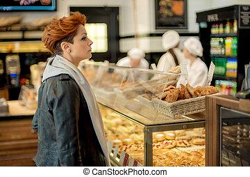 Woman choosing bakery items in a shop