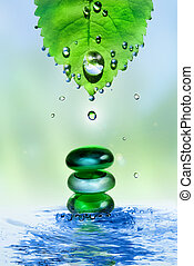 balancing spa shiny stones in water splash with leaf and drops