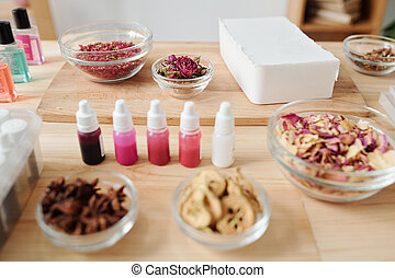 Bar of hard soap mass, spices and dry flowers, small bottles with colors