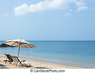 Beach chairs and umbrella on white sand beach