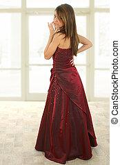 Teen girl in burgandy formal dress. Full body standing.