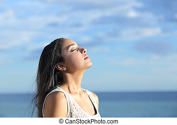 Beautiful arab woman breathing fresh air in the beach with a cloudy blue sky in the background