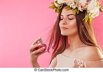 Beautiful woman in wreath applying perfume. Natural cosmetics concept