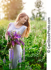 beautiful woman with bouquet of wildflowers in meadow