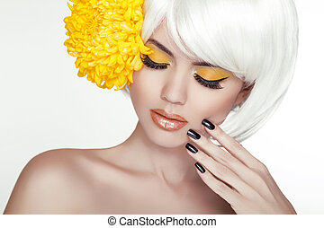 Beauty Blond Female Portrait with yellow flowers. Beautiful Spa Woman Touching her Face. Makeup and manicured nails. Perfect Fresh Skin. Isolated on white background