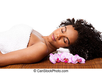 Beautiful happy peaceful sleeping woman at a day spa, laying on bamboo massage table with head on pillow wearing a towel and orchid flowers around, isolated.