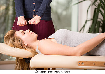 Young woman relaxing during bioenergy therapy session