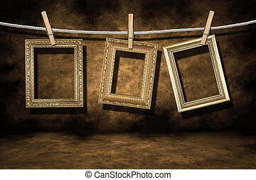 Blank Empty Gold Photo Frames on a Distressed Grunge Background Hanging on a Rope