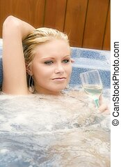 Blond girl in hot tub with wine