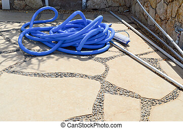 Blue plastic long large corrugated hose for cleaning the pool wash and watering the plants