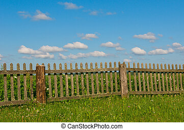 Blue sky, green grass and fence