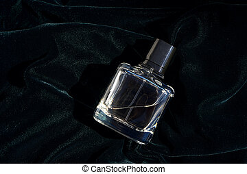 Bottle of Perfume - Fragrance bottle in dark green and blue color cloth background.