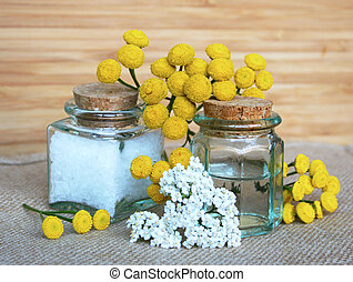 Bottles of essential oil and sea salt in spa composition