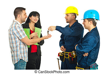 Builder men team give house keys to a couple