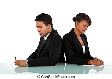 Business couple writing on forms