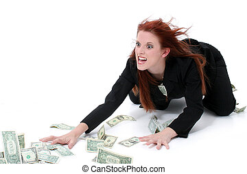 Crazed Business Woman Grabbing Money From Floor. Very funny expression on model's face. Shot in studio over white.