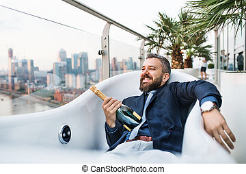 Businessman lying in empty hot tub, London view panorama in the background.