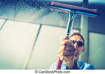 Caucasian Men Removing Water From His Car Window Right After Washing. Vehicle Window Cleaning Theme.