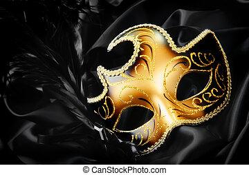 Ornate carnival mask on black silk background.
