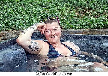 caucasian woman relaxing in a hot tub outdoor