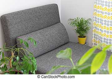 Gray chaise longue and lots of green plants in the living room.