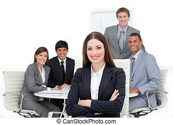 Charismatic female executive sitting in front of her team in a meeting