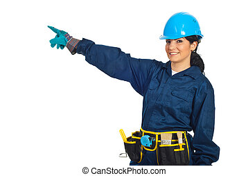 Cheerful constructor worker woman pointing to left side on copy space isolated on white background