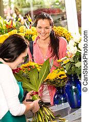 Cheerful woman buying bouquet flower shop florist
