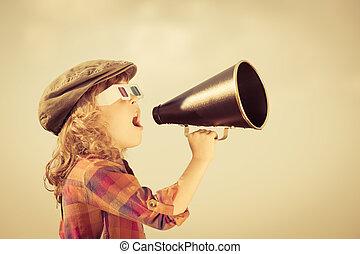 Child shouting through vintage megaphone. Cinema concept. Retro style