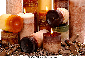 Assortment of chocolate scented candles arranged among chocolate bars and morsels.