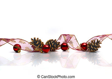 Christmas decoration with ribbon, cones and red balls reflected on white background