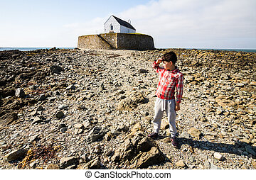 Church in the sea or on a beach, small boy looking at view.