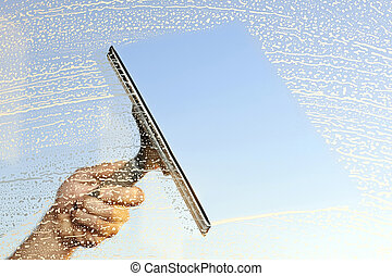 A hand and a squeegee cleaning windows