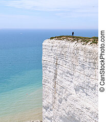 woman's figure standing on a white steep cliff in Beachy Head