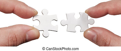 Close up Connection. Hands trying to fit two puzzle pieces together. Hands trying to attach two jigsaw puzzle pieces isolated on white
