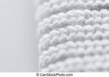 handicraft, knitwear and needlework concept - close up of white knitted item