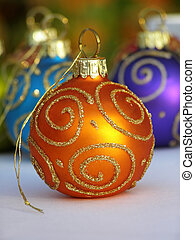 Close-up of orange Christmas bauble with swirl decoration in gold